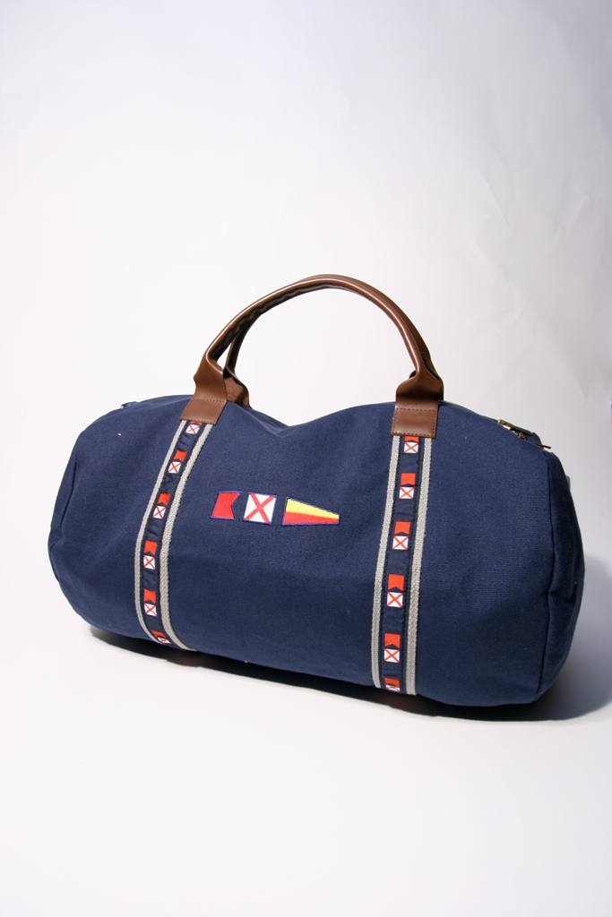 Style #2160: Custom yacht duffel made of 18-oz cotton canvas, rich leather handles, nautical-themed custom woven ribbon, and embroidery on front pocket. Made in USA.